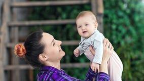 中等抱着她的小婴孩的特写镜头愉快的母亲微笑和做吹享受母性 影视素材