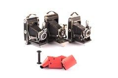 中等格式减速火箭的照相机的减速火箭的120影片在与阴影,在背景的三台模糊的葡萄酒照相机的白色背景,能m 图库摄影