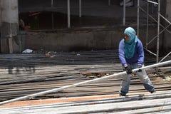 中部作为堆积脚手架管子的民工的年迈的肥胖妇女工作在大厦工作地点,为一个人适合的工作 免版税库存图片