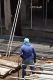 中部作为堆积脚手架管子的民工的年迈的肥胖妇女工作在大厦工作地点,为一个人适合的工作 免版税库存照片