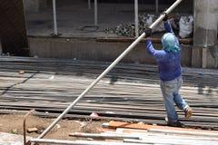 中部作为堆积脚手架管子的民工的年迈的肥胖妇女工作在大厦工作地点,为一个人适合的工作 图库摄影