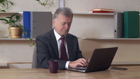 中部使用个人计算机的年迈的企业家在工作 股票视频