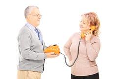 中部使用老电话的年迈的夫妇 免版税图库摄影