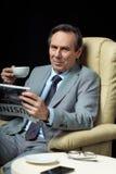 中部变老了商人用坐在扶手椅子的咖啡和报纸 免版税库存图片