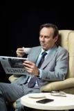 中部变老了商人用坐在扶手椅子的咖啡和报纸 库存图片