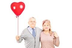 中部变老了在拿着一个红色心脏气球的拥抱的夫妇 库存照片