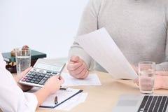中部变老了夫妇签署的合同在保险机构 免版税库存照片