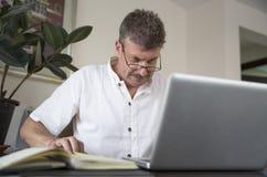 中部变老了工作在这台计算机的人在他的家庭办公室 库存图片