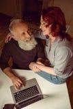 中部变老了拥抱的夫妇坐在桌上和,当在家时使用膝上型计算机 库存图片