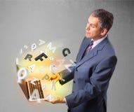 中部变老了拿着有五颜六色的信件的商人膝上型计算机 免版税库存图片