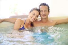 中部变老了放松和享用极可意浴缸的夫妇 免版税库存照片