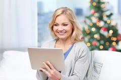 中部变老了有片剂个人计算机的妇女在圣诞节 库存图片