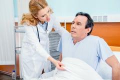 中部变老了有痛苦的病人坐床,帮助他的医生 库存照片