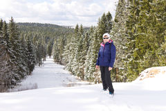 中部变老了站立在小山顶部的女性旅客反对冬天森林背景 库存图片