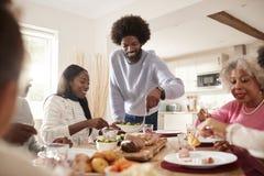 中部变老了黑人雕刻的和服务的肉在星期天与他的伙伴、孩子和他们的祖父母,正面图的家庭晚餐 免版税库存图片