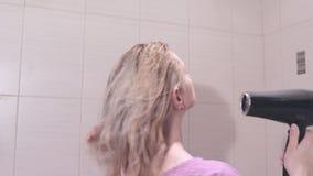 中部在卫生间里变老了烘干她的有一hairdryer的白肤金发的妇女头发 股票视频