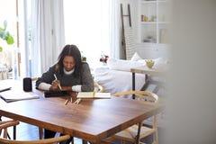 中部在她的餐厅变老了坐在一张桌上的非裔美国人的妇女使用有片剂计算机的一支铁笔,看见从门道入口 免版税库存图片