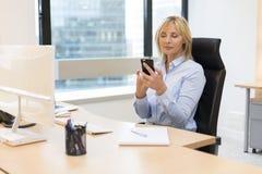 中部工作在办公室的年迈的女商人 使用Smartphone 免版税库存图片