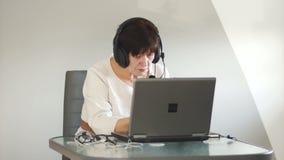 中部年迈的女性给忠告顾客用途耳机 顾问在支助服务工作 股票视频