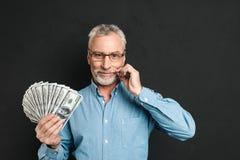 中部的图象变老了有拿着金钱f的灰色头发的富人60s 库存照片