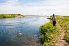 中部年迈的人钓鱼从河的被捉住的三文鱼 免版税库存照片