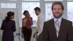 中部年迈的商人姿势在办公室