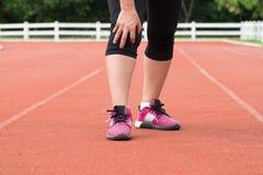 中部年迈的妇女赛跑者膝盖痛苦 免版税库存照片