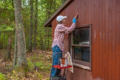 中部年迈的妇女绘画棚子 免版税库存图片