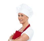中部年迈的确信女性厨师摆在 免版税库存照片