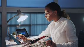 中间关闭在白色外套和防护玻璃的检查主板的电子的女性工程师与