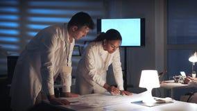 中间关闭检查控制电子学计划的两位电子工程师在一个现代实验室 影视素材