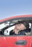 中间变老的人在汽车打喷嚏 免版税库存图片