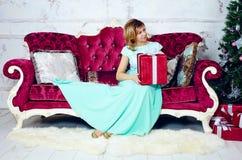 中间妇女画象坐有圣诞节礼物的沙发 库存照片