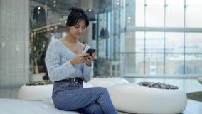 中间射击年轻亚裔女孩短信的坐在购物中心休息区域  影视素材