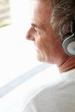 中间年龄人佩带的耳机 免版税图库摄影