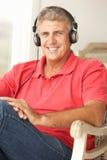 中间年龄人佩带的耳机 免版税库存照片