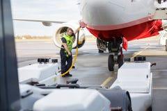 中间成人在跑道的成员充电的飞机 库存图片