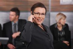 中间成人女实业家联系在移动电话 库存照片