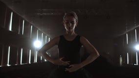 中间计划慢动作:一个年轻芭蕾舞女演员女孩在芭蕾舞短裙和Pointe鞋子进行在阶段的优美的运动  影视素材