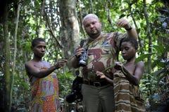 中非共和国- 2008年11月2日:白人游人和妇女从Bakf的侏儒部落在森林里 免版税库存照片