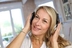 中年与headphoes的妇女lsitening的音乐 免版税库存照片