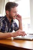中年人与膝上型计算机和巧妙的电话一起使用 免版税库存照片
