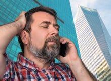 中年人发表演讲关于一个手机 免版税图库摄影