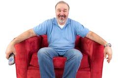 中年人坐一把红色扶手椅子 免版税库存照片