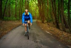 中年人骑沿森林公路的一辆路自行车 免版税库存图片