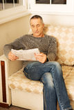 中年人读书报纸在家 免版税图库摄影
