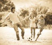 中年使用与足球的夫妇和少年 免版税库存图片