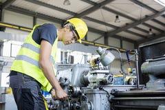 中间在金属工业的成年男性工作者运行的机械侧视图  免版税图库摄影