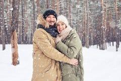 中年夫妇拥抱,当通过时享受冬天步行 免版税库存图片