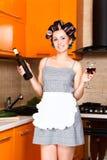 中年主妇在有瓶和杯的厨房里酒 免版税库存照片